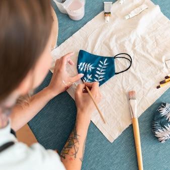 Женщина рисует маску крупным планом