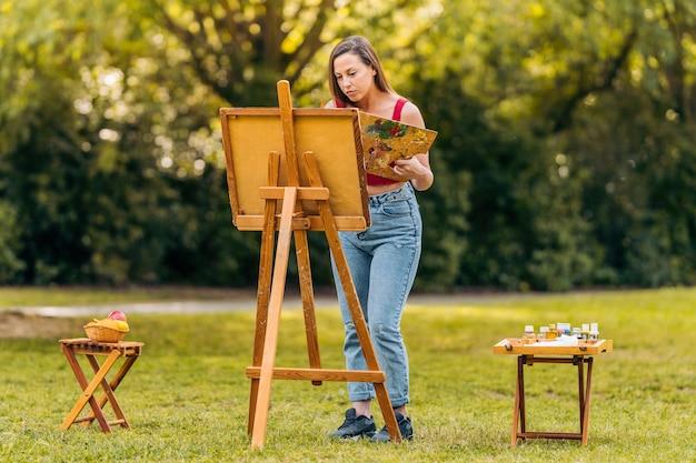 공원에서 캔버스에 그림을 그리는 여성, 페인트 냄비와 도구가 있는 사이드 테이블 2개