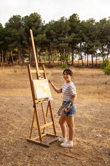 自然の中で屋外のキャンバスに絵を描く女性