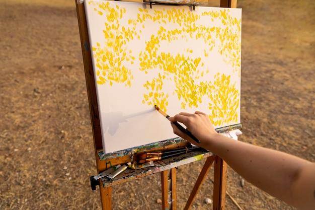 屋外のキャンバスに絵を描く女性