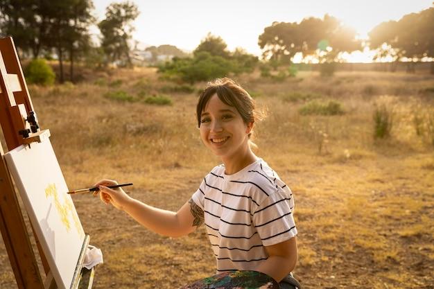 自然の中で外のキャンバスに絵を描く女性