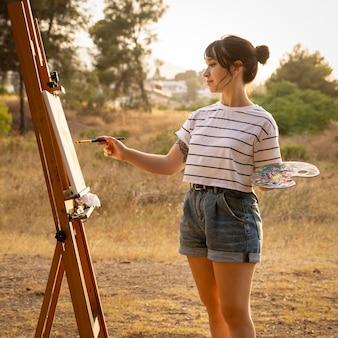 外のキャンバスに絵を描く女性
