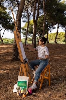 パレットとキャンバスに屋外で絵を描く女性