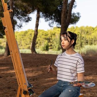 キャンバスに屋外で絵を描く女性