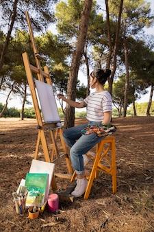 屋外で絵を描く女性