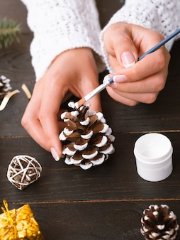 Woman painting a pine cone