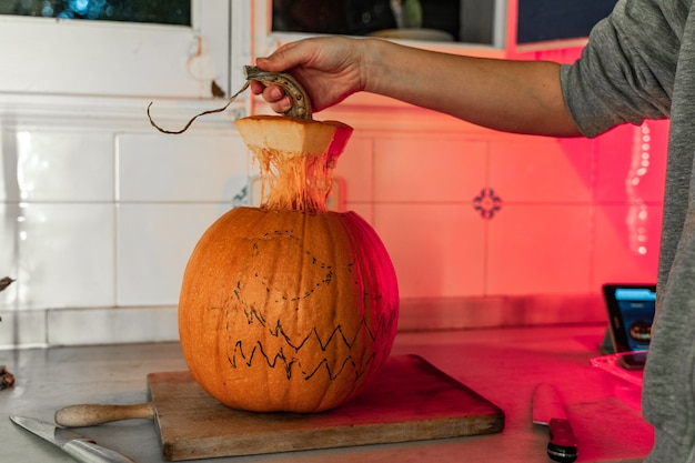 Woman painting pumpkin face and making jack o lantern side for halloween