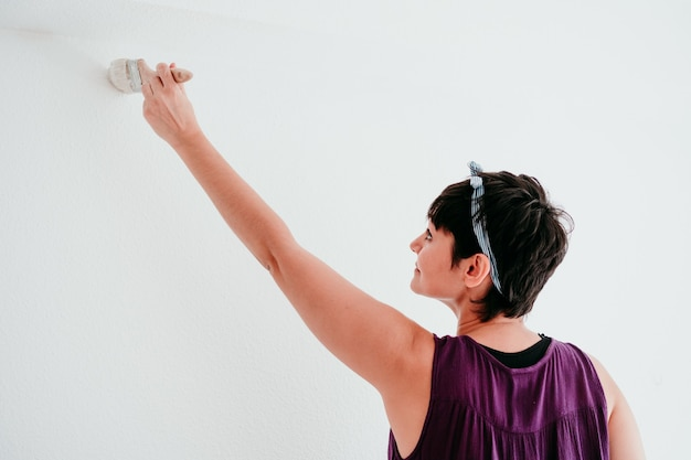 Woman painting the room walls