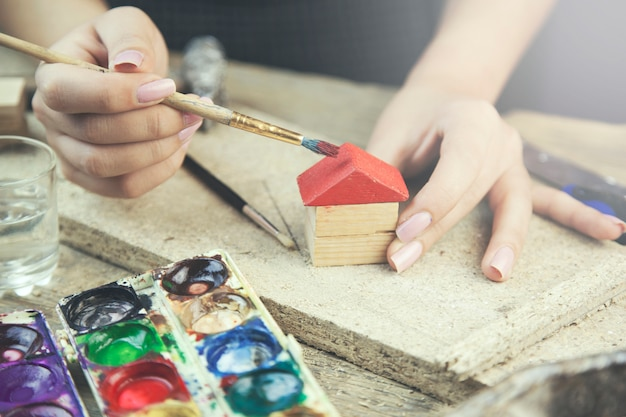 Woman painting small house