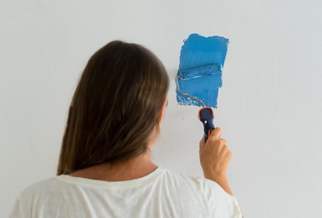 Женщина красит стену в синий цвет