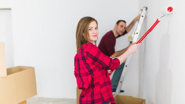 Woman painting wall near man