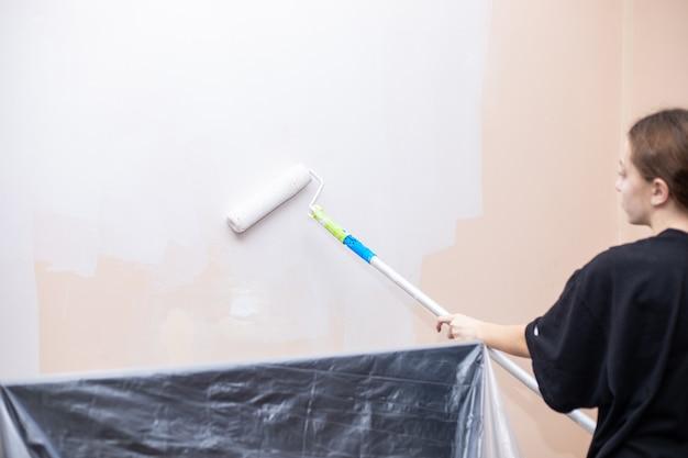 여자 그림 벽입니다. 페인트 브러시 그림 벽을 가진 여자의 후면 볼 수 있습니다. 수리 및 주택 개조