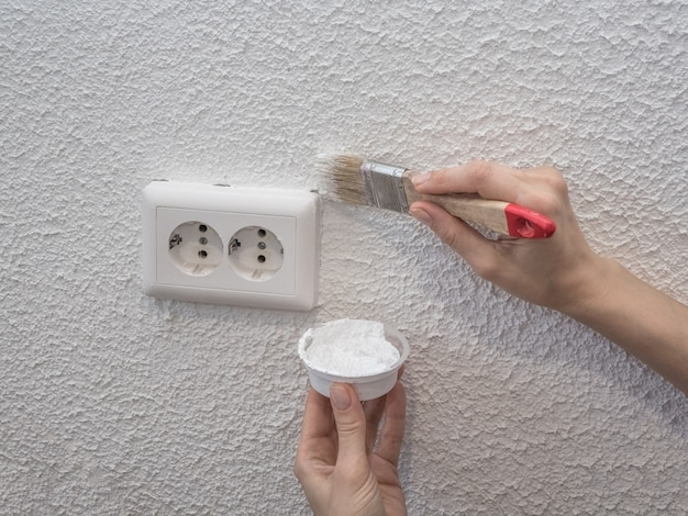 Woman painting the wall. restoration of the painted white walls.