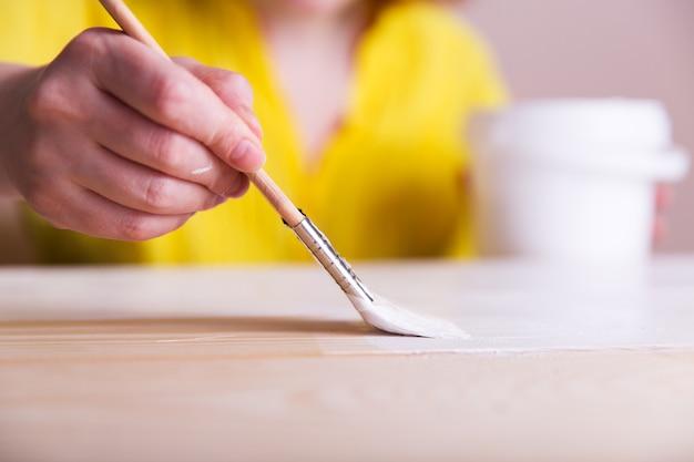 絵筆で絵を描く女性木の板