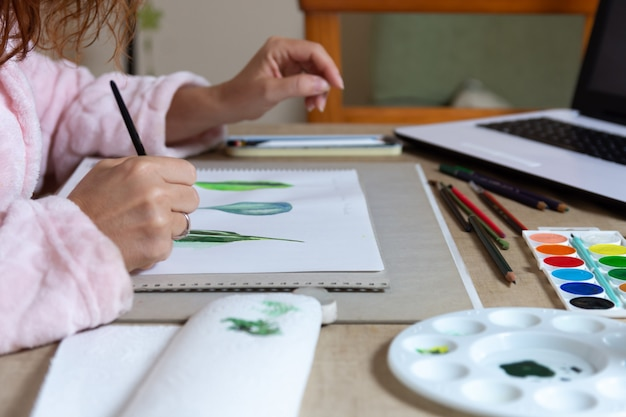 Woman painting with watercolors at home