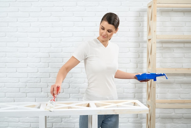 Woman painting with white color old wooden rack
