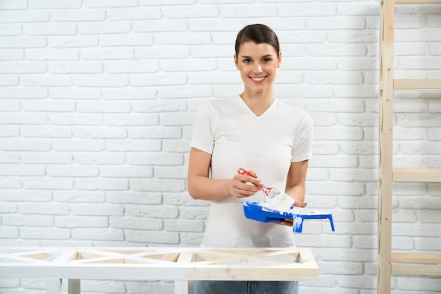 Woman painting with white color wooden rack