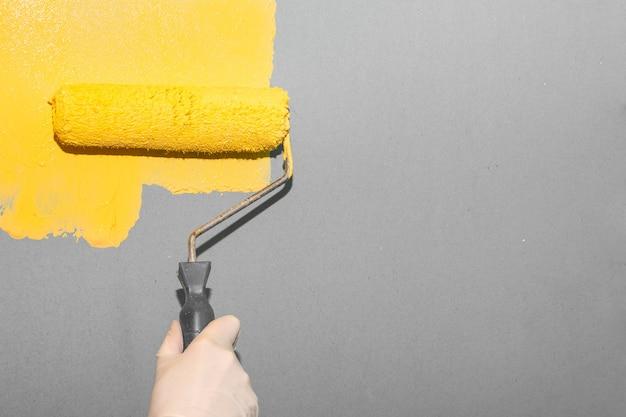 Женщина красит серую стену валиком в желтый цвет