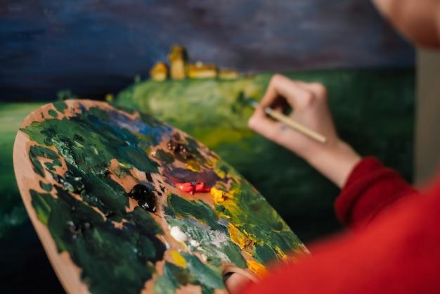 女性は水彩絵の具アートで絵を描く