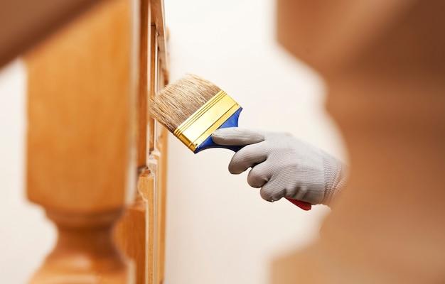 女性はブラシでニスの木の板を描く