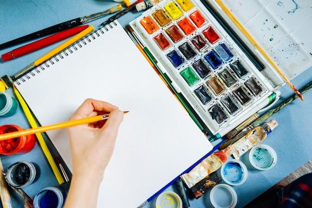 女性は白い紙にブラシと水彩絵の具でアーティストを描く
