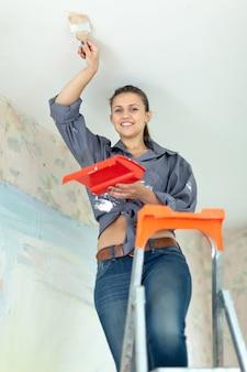 Женщина рисует потолок кистью