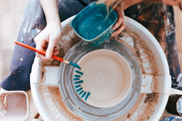Woman paints a ceramic plate with a brush and blue paint
