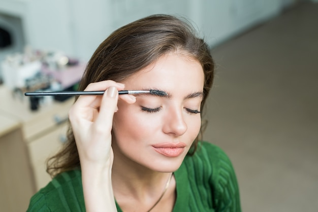Woman paints the eyebrows