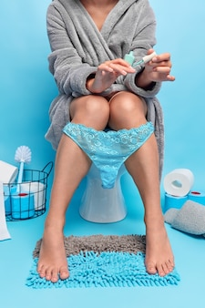 Woman paints nails while defecating on toilet bowl wears bathrobe and lacy panties poses in lavatory room on blue
