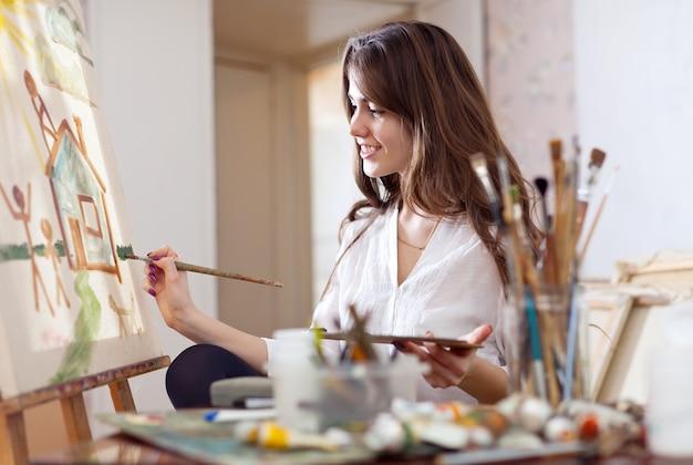 Woman paints on canvas