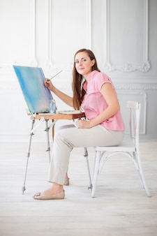 Woman paints picture on canvas