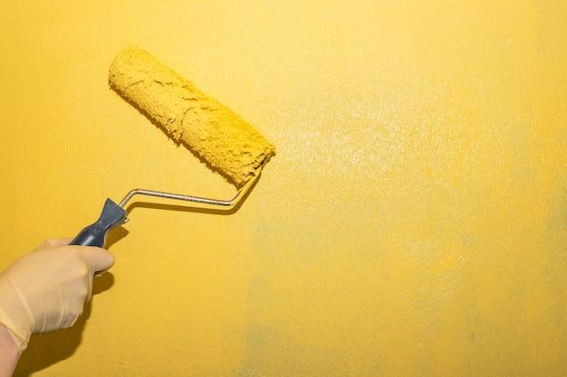 Женщина красит стену валиком желтой краской