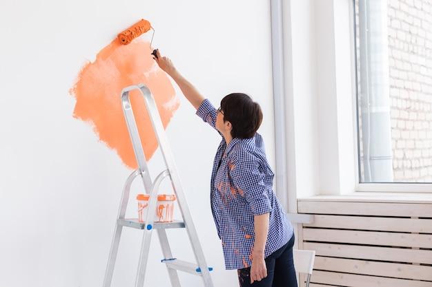 Женщина красит стену