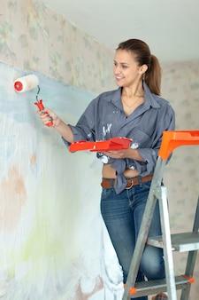 女性は家のローラーで壁を塗る