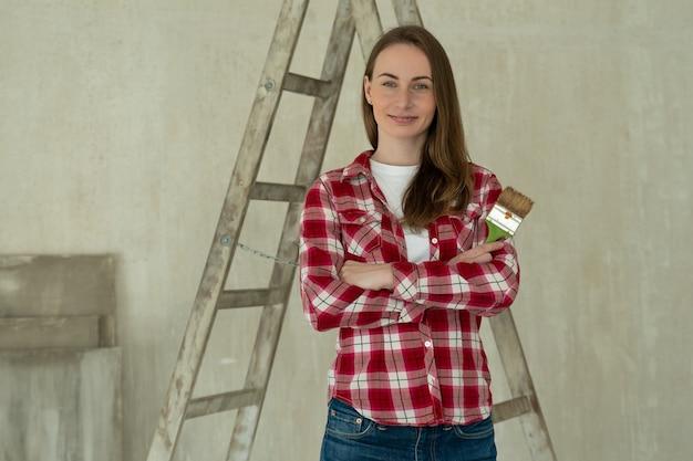 Женщина красит стены дома, проводит ремонт кистей и концепцию ремонта дома