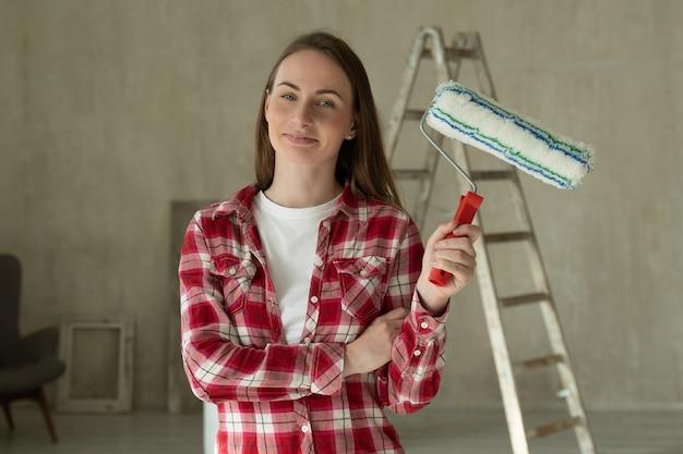 Женщина красит стены дома, держит в руках концепцию ремонта и ремонта дома