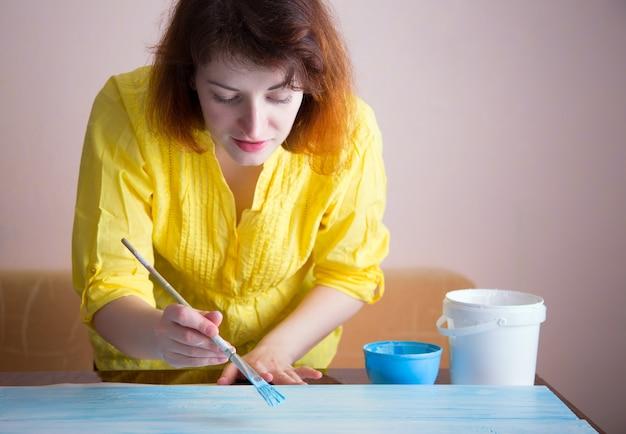 여자 페인트 브러시로 나무 판