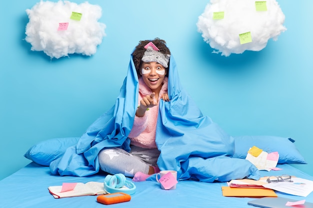 Woman in pajama points with great surprise prepares creative project poses at bedroon on comfortable bed makes notes at stickers works from home