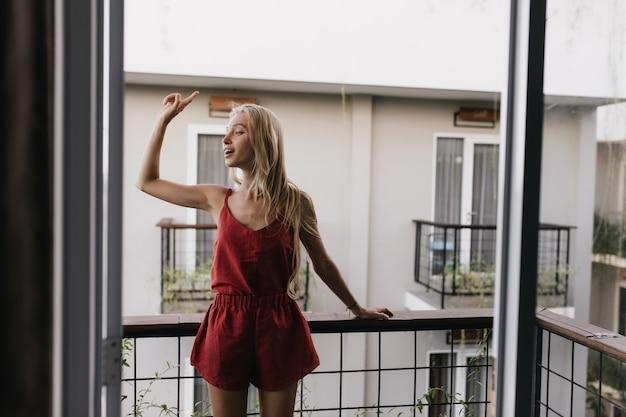 Donna in pigiama in piedi sul balcone e guardandosi intorno. modello femminile emozionante con capelli biondi lunghi che gode del mattino.
