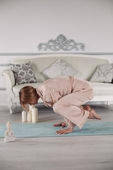 Donna in pigiama che fa esercizio di yoga nel soggiorno del suo appartamento mentre si appoggia le mani sul tappetino. concetto di stile di vita sano. fitness mattutino