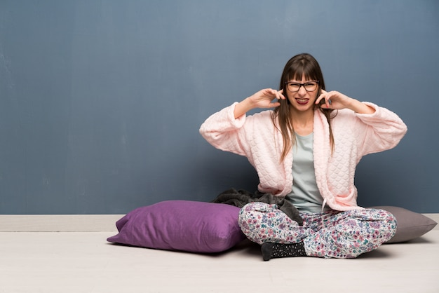 Woman in pajamas on the floor frustrated and covering ears with hands