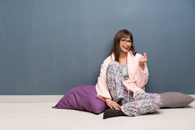 Woman in pajamas on the floor making money gesture
