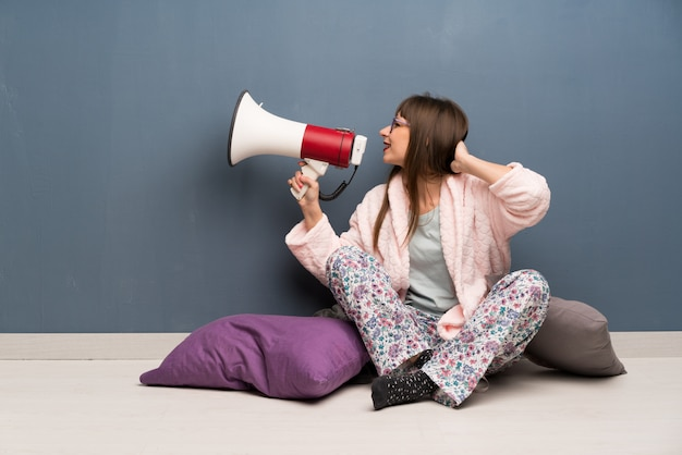Woman in pajamas on the floor shouting through a megaphone