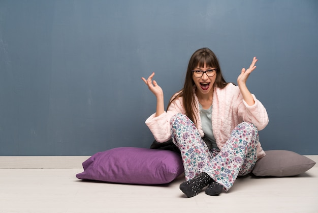 Woman in pajamas on the floor with shocked facial expression