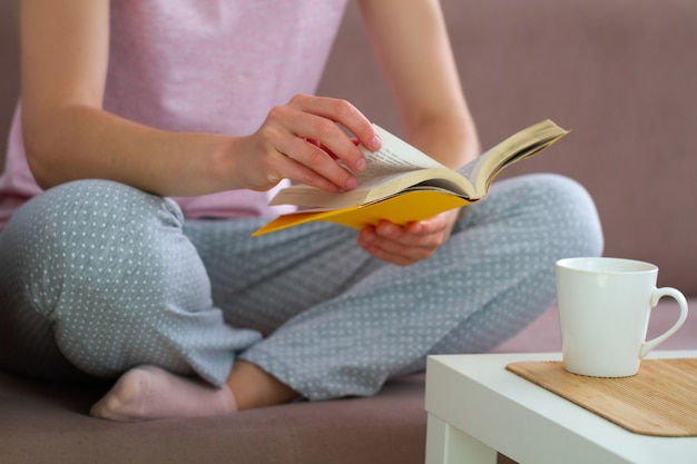 Woman in pajamas is resting and reading a favorite book at home. cozy pastime