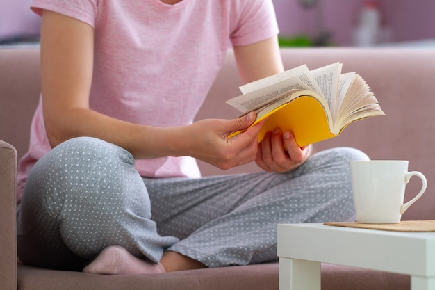 Woman in pajamas is resting and reading a favorite book at home
