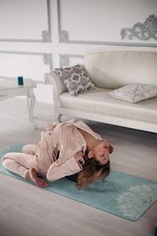 Donna in pigiama seduta sul tappeto e facendo il piegamento all'indietro durante gli esercizi la mattina a casa. concetto di stile di vita sano. fitness mattutino