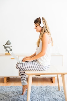 Woman in pajamas sitting with laptop and headphones