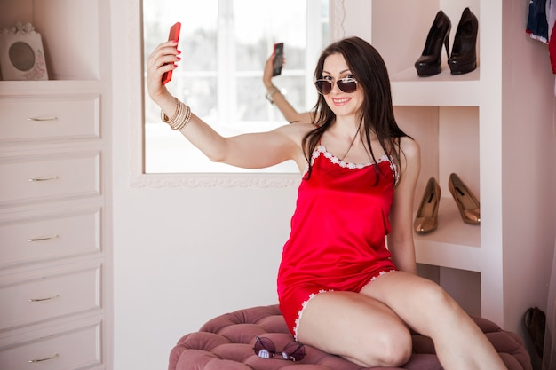 Woman in pajamas trying on sunglasses and taking a selfie