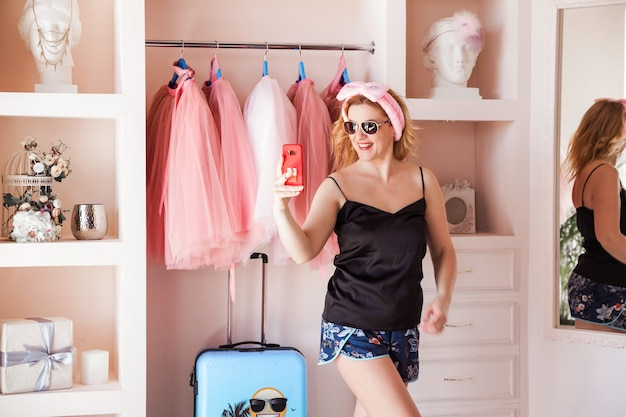 Woman in pajamas trying on sunglasses and taking a selfie.